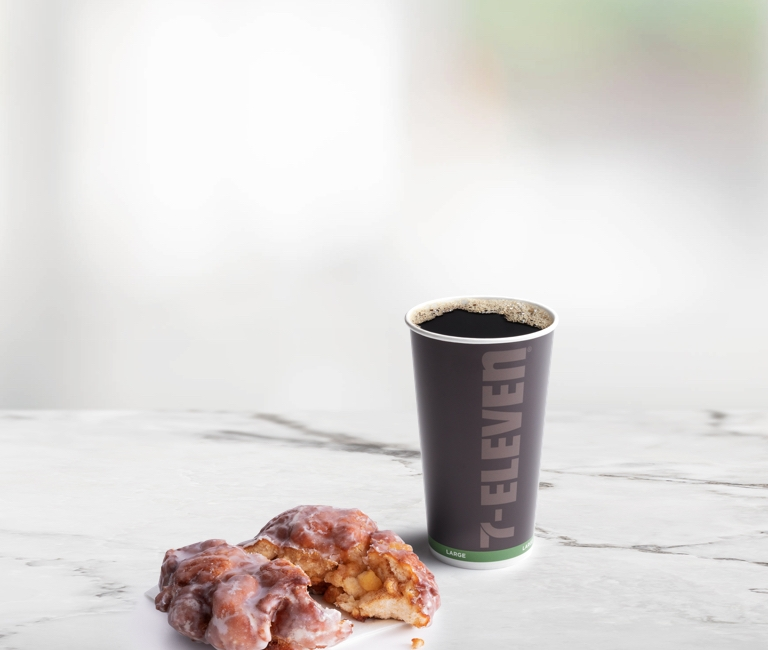 Kenya Single Origin Black Coffee in a To Go Cup with an Apple Fritter