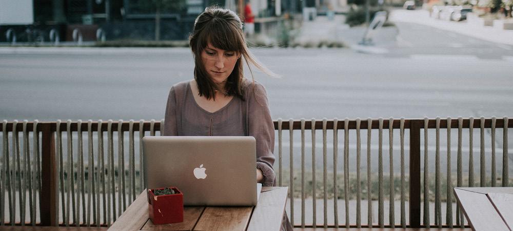 Femme travaillant sur son ordinateur à la terrasse d'un café