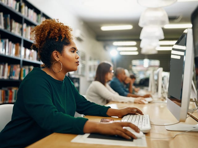 African American lady is studying at a library computer immersing herself in language study and understanding how to learn a language fast.