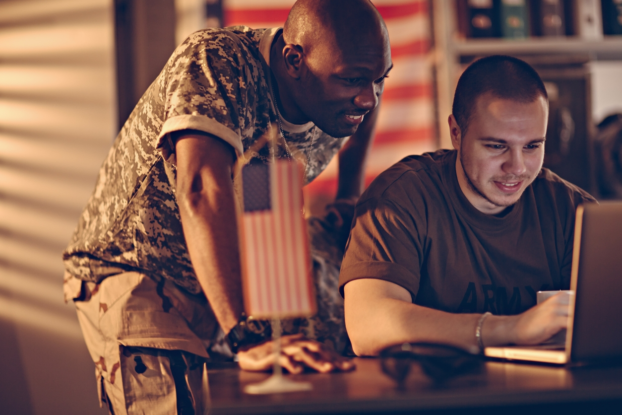 Two smiling military personnel learning a language online.