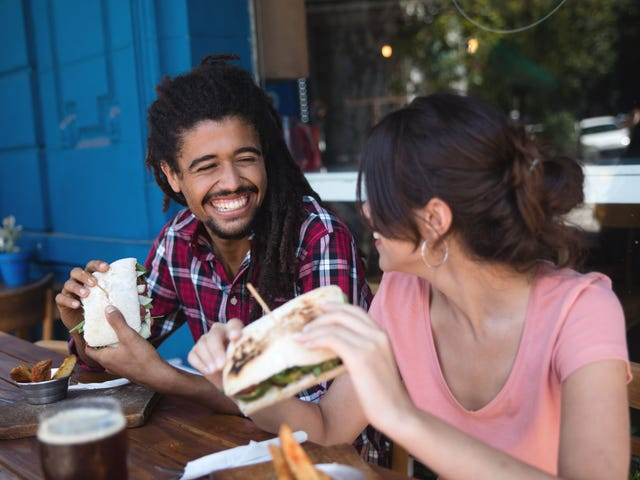 A happy young man with dreadlocks having a sandwich lunch with a smiling new female friend in a pink t-shirt, a shining example of how to make friends in a new country.