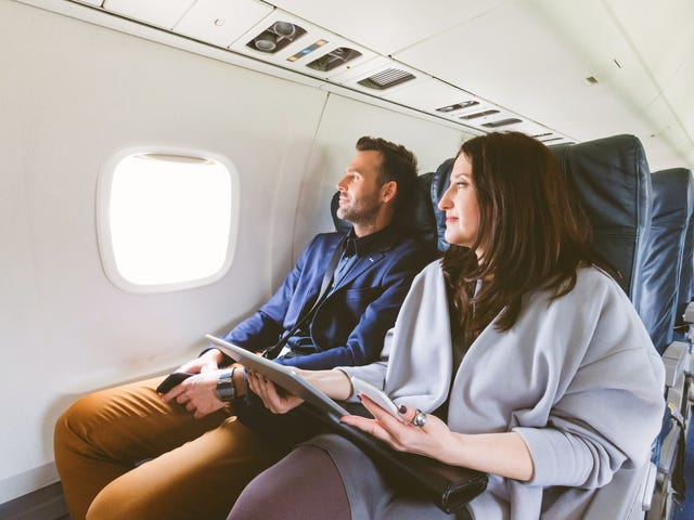 A young couple is sitting on a plane and looking out the window with anticipation, holding their moving abroad checklist.