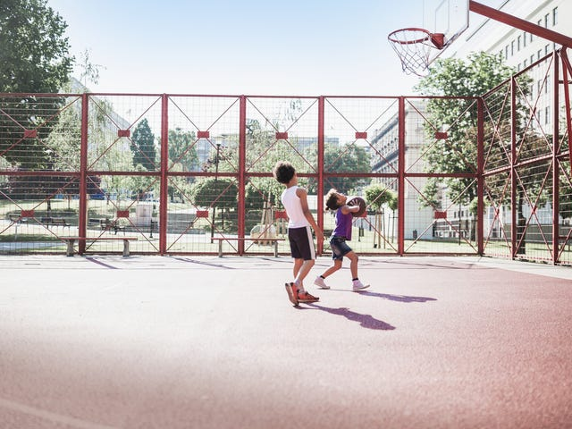 Two young boys playing basketball and enjoying the fun, active benefits of summer camp.