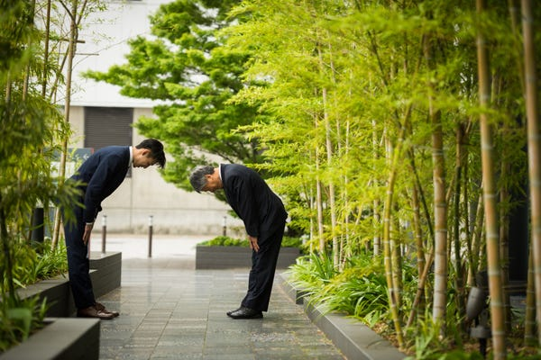 Colleagues greeting each other with a respectful bow, surrounded by bamboo trees - an example of cultural differences in communication.