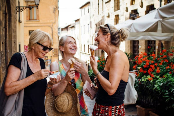 Three happy laughing older women in a foreign country, exploring the best places to retire abroad.