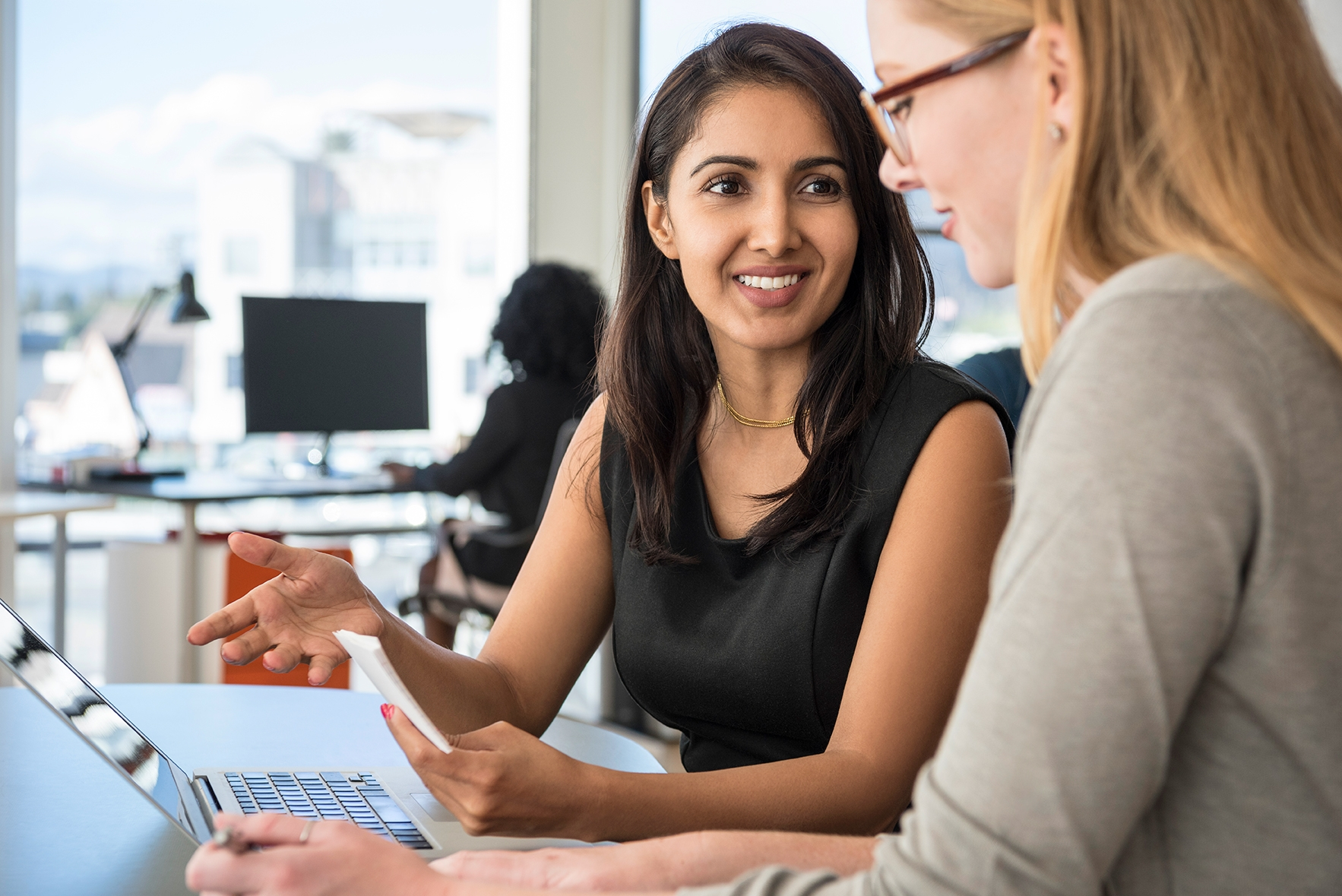 Two ladies of different ethnic backgrounds smiling and chatting over a laptop in an office space.