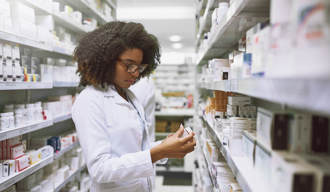 Pharmacist looking for Rx medication price without insurance. The pharmacist is a Black woman wearing a white coat, holding a bottle in her hands.  Shelves of medications surround her in the pharmacy.