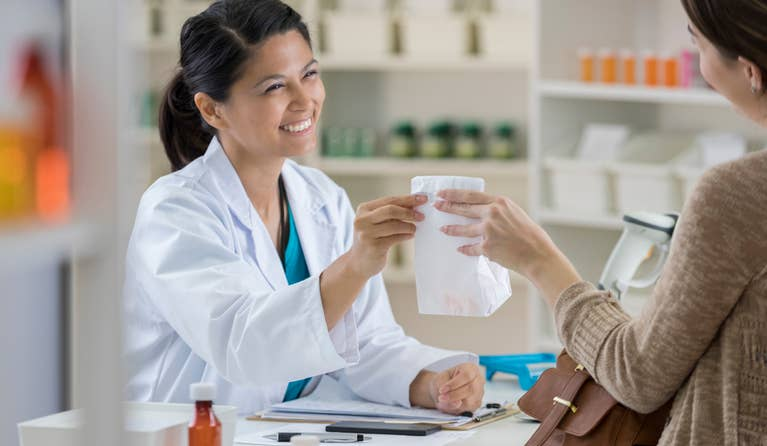 Female pharmacist checking out a customer