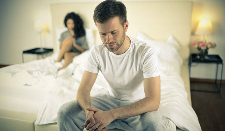 Man facing away from his wife in bed due to worrying about his erectile dysfunction