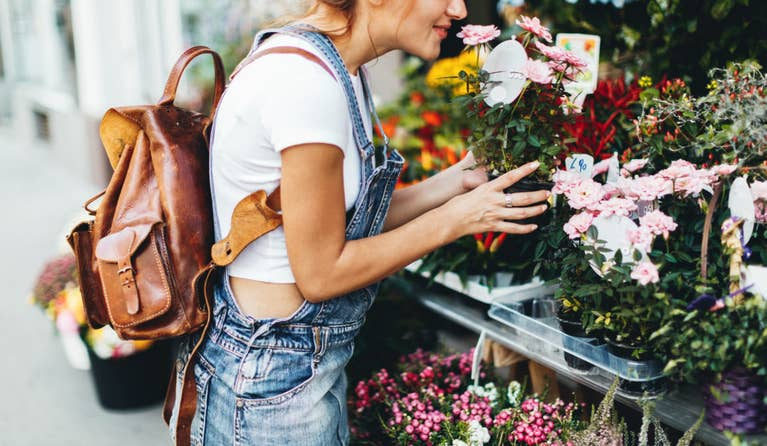 Woman smelling flowers that on sale on the street