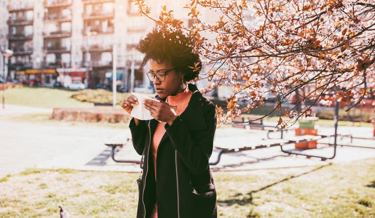 Woman holding a tissue and about to blow her nose due to allergies while walking outside in a park