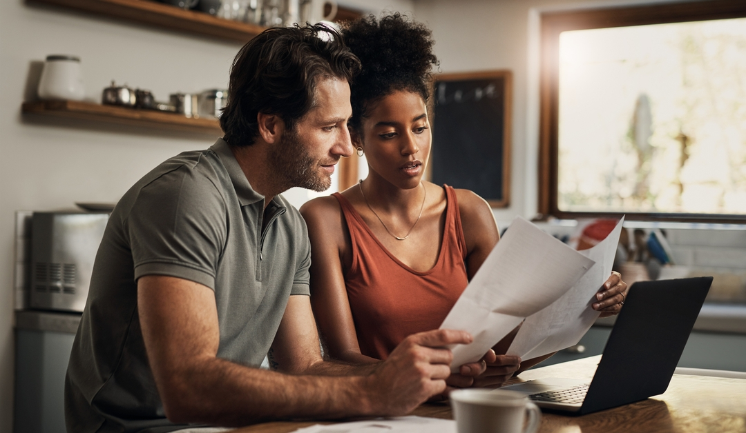 Couple in front of computer looking at papers regarding open enrollment for health insurance