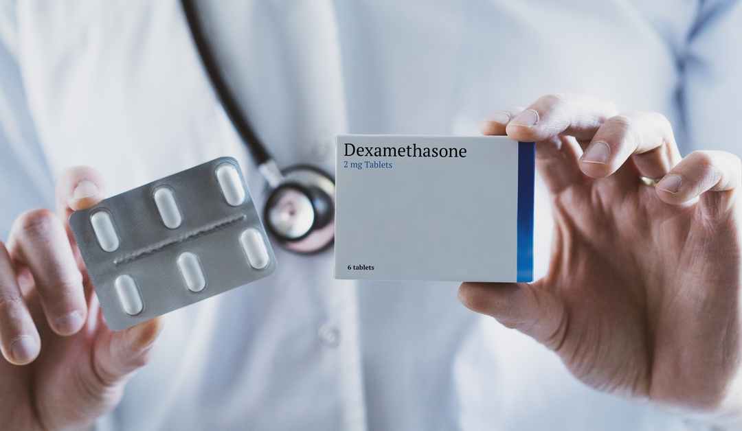 Pharmacist holding a 6 pack of dexamethasone with the box labeled