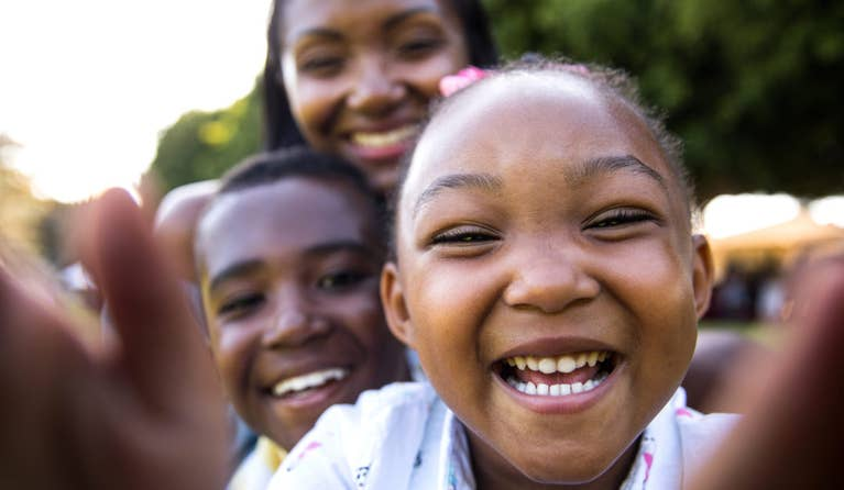 Close up look of two black children and mother happy because they are able to receive medical treatment