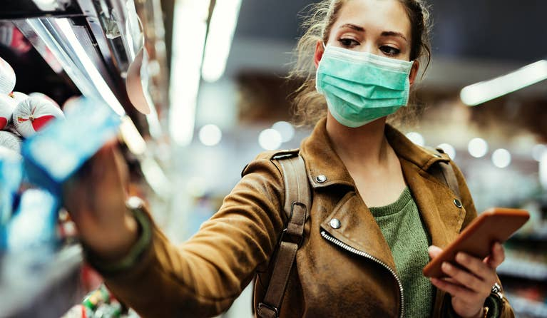 Woman wearing a face mask at a store and is also holding her phone.