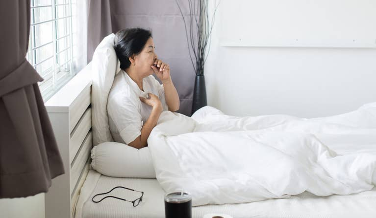 A woman in bed who is coughing due to dry cough