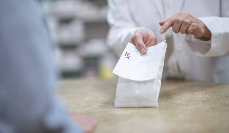 A pharmacist holds a bag of atorvastatin at the pharmacy check-out, perhaps for a patient without insurance.
