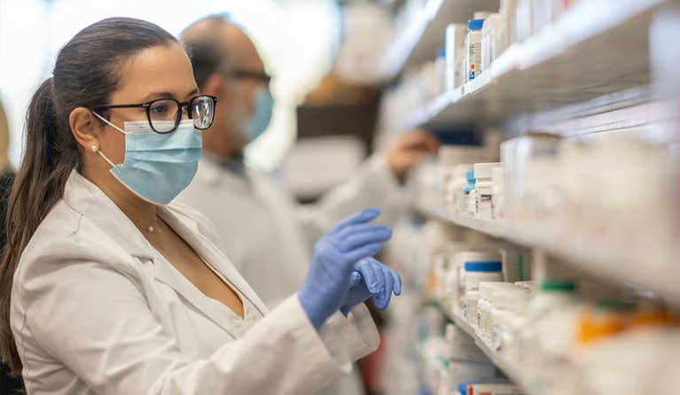 Pharmacist with a mask on looking at a shelf at the pharmacy