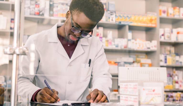 A pharmacist writes something on a clipboard, perhaps as he fills a prednisone prescription for an uninsured patient.