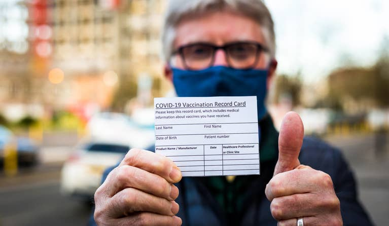 A man with a mask holding his COVID-19 Vaccination Record Card in one hand and giving a thumbs up with his other hand.
