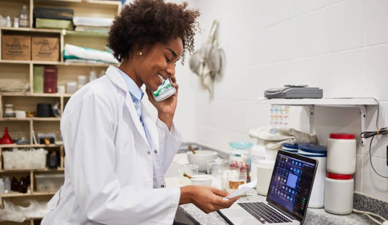 A pharmacist smiles as she takes a phone call from a patient, perhaps asking about the cost of escitalopram without insurance. The pharmacist is holding a phone to her ear as she stands near her computer in the pharmacy.