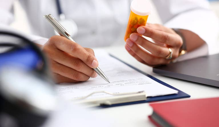 A doctor holding erectile dysfunction medication in one hand and prescribing the medication to his patient in the other