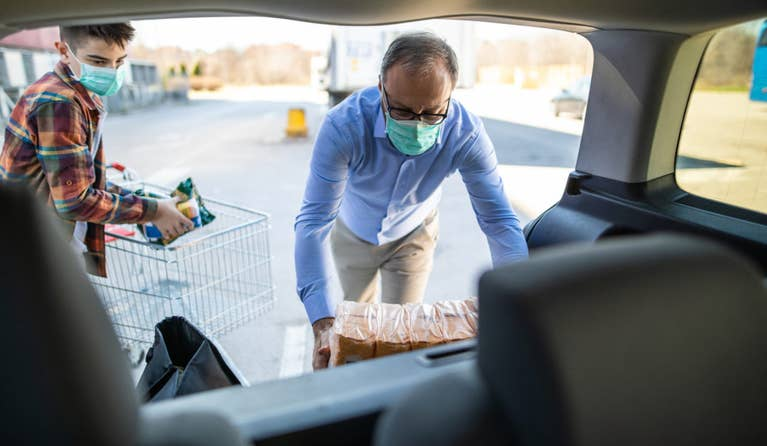 Two men wearing masks are loading their groceries in the car during COVID-19