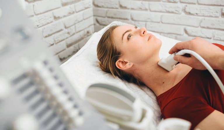 Lady on medical bed getting her thryoid checked with medical device