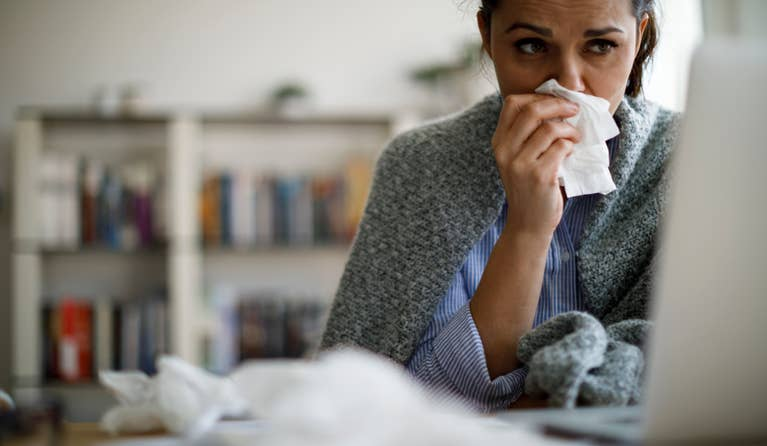 A woman bundled in a blanket looking at her computer and blowing her nose while fighting off the flu