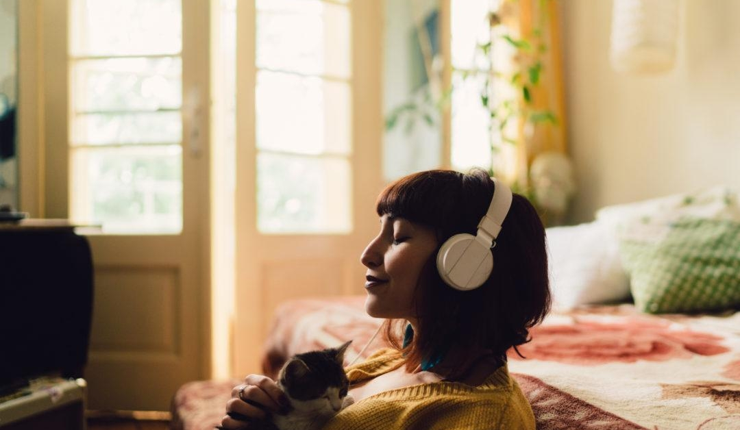 A young woman is sitting in her home with her eyes closed, wearing headphones. She is using a meditation app as a free resource to support mental health during COVID-19.
