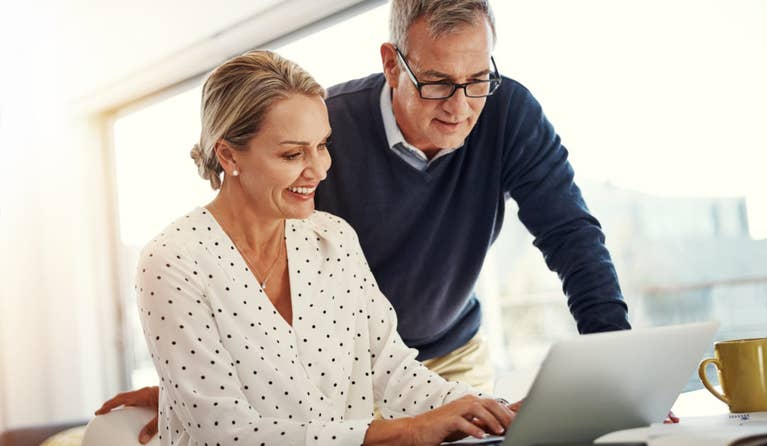 Older couple looking at a computer trying to figure out how to save on a high deductible health plan