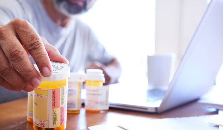 A man who is looking at his prescriptions has his computer opened and is researching if their patents have expired.