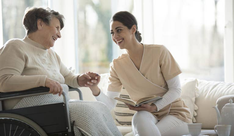 A nurse holding hands with a lady who has dementia during COVID-19