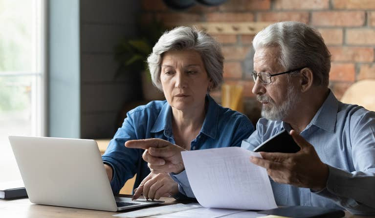 Senior couple looking at medical bills on the computer