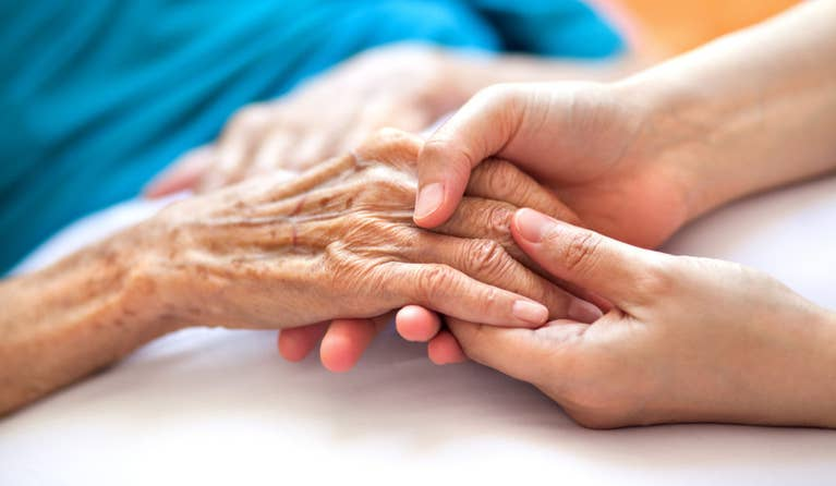 A younger woman holding the hands of an elderly woman suffering from Alzheimer's disease