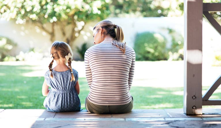 A mom talking to her daughter about mental health in their backyard.