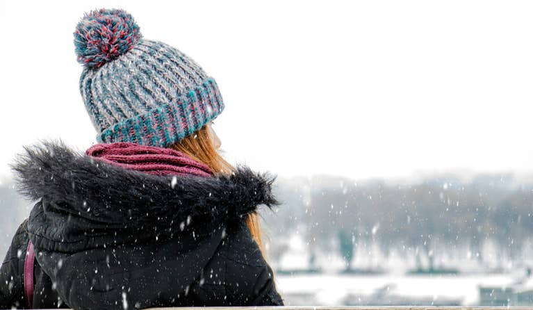 Woman standing outside while it is snowing