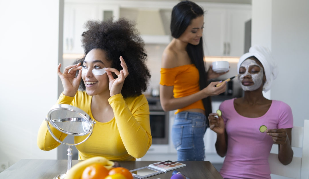 Three young Black women apply cosmetics and a face mask in a bathroom, perhaps as a way to boost their moods during the winter slump.