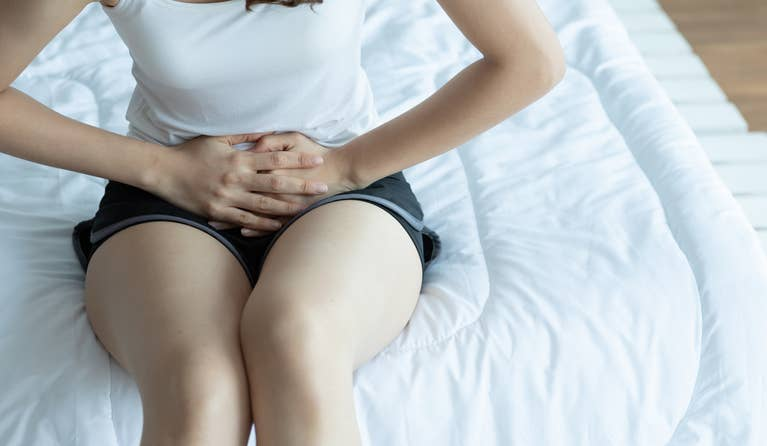 a woman hunched over on her bed due to a urinary tract infection