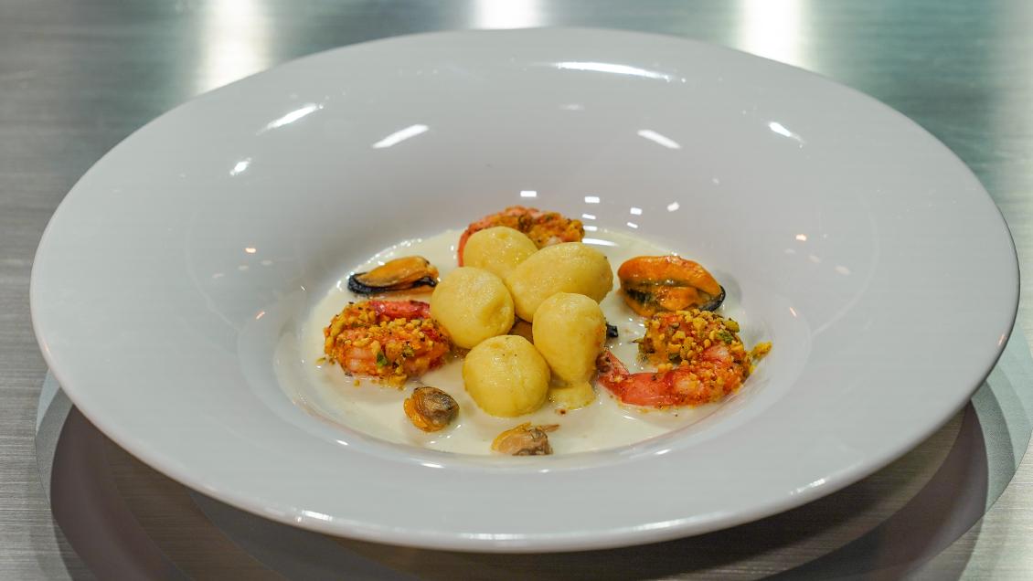 Gnocchi di patate e caciocavallo su crema di sedano rapa con cozze, vongole e gamberoni croccanti