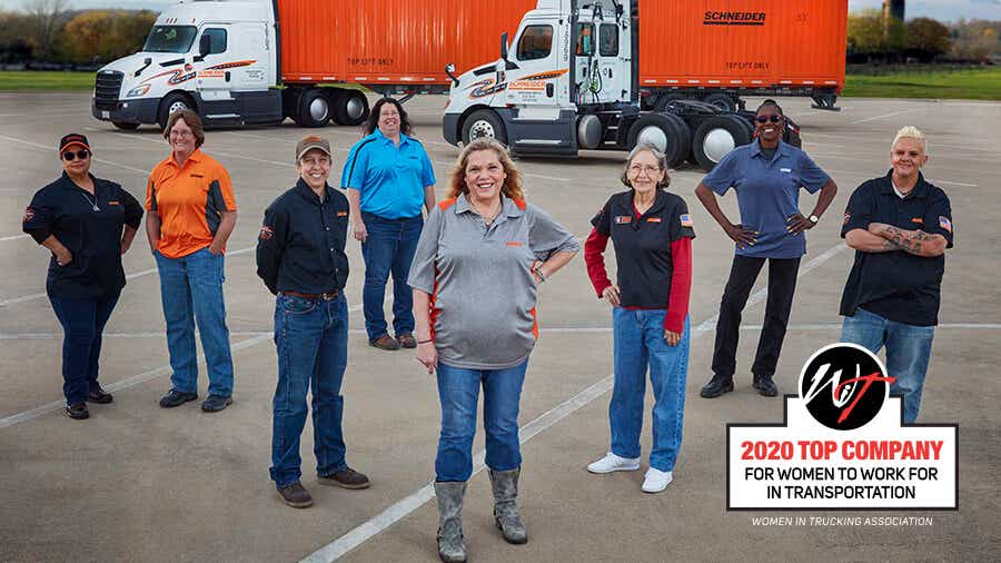 A group of Schneider women truck drivers stand proudly in front of a Schneider tractor, container and day cab