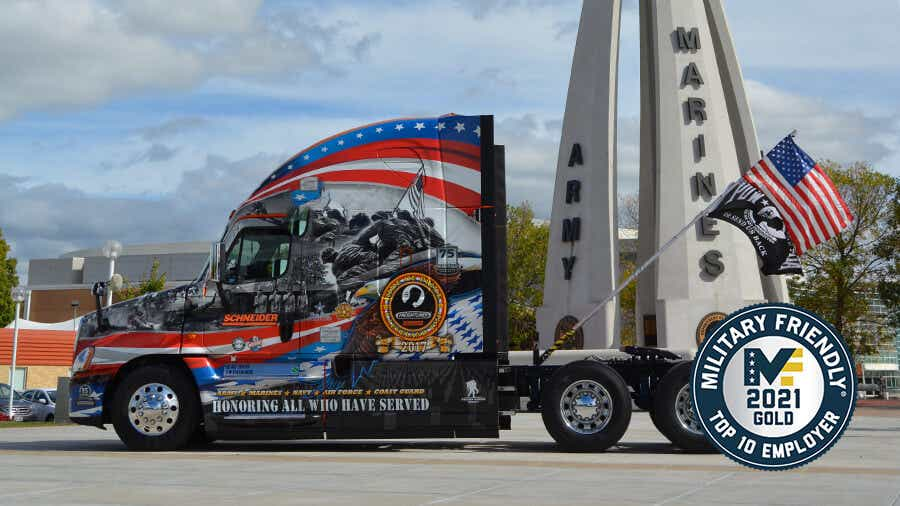 One of Schneider's Ride of Pride (patriotically decorated) tractors is parked besides a memorial to the U.S. Armed Forces.