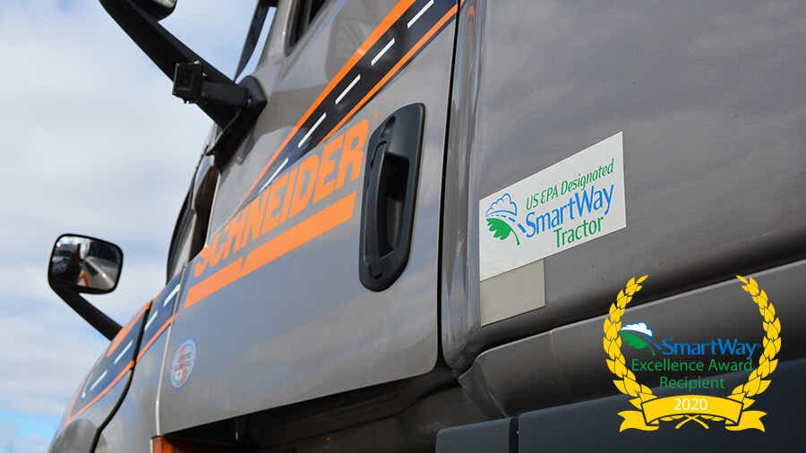 A decal with Schneider's SmartWay designation is proudly displayed on a company tractor