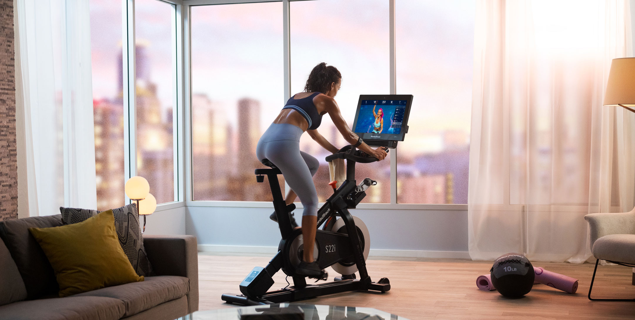 Woman riding exercise bike in her bedroom