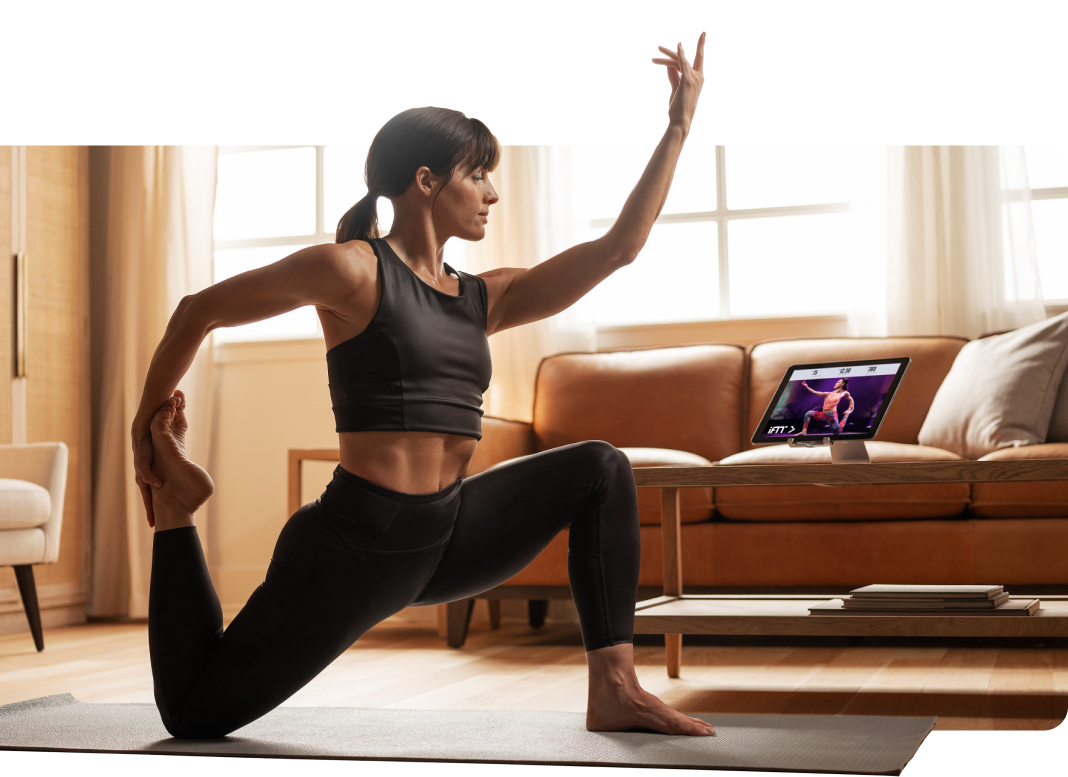 Woman does yoga pose while watching iFIT on tablet