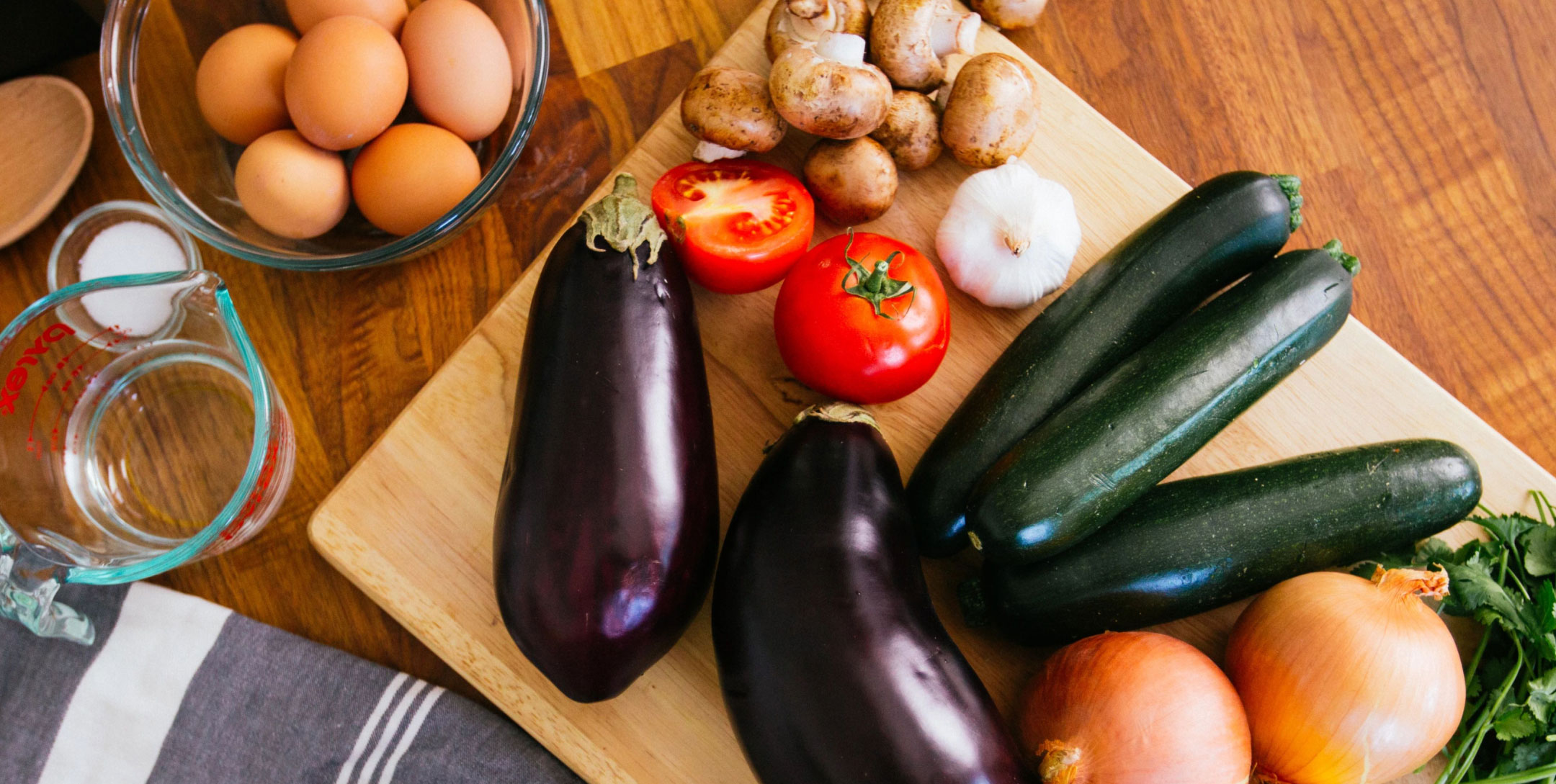 Fresh vegetables on cutting board and eggs in bowl