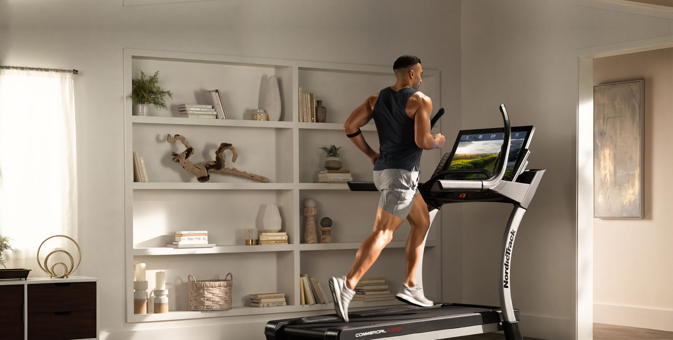 Man running on iFIT treadmill in front of bookshelf