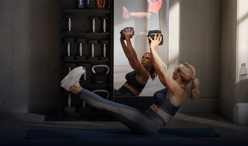 Woman performing V crunches in front of NordicTrack mirror