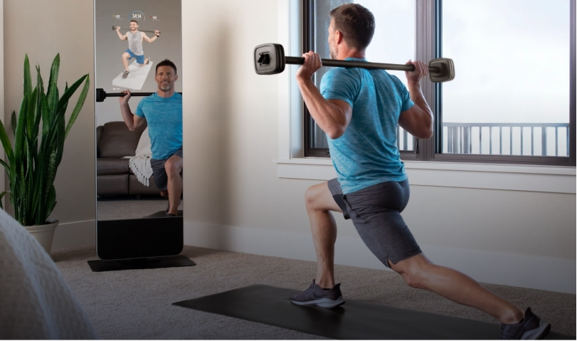 Man doing lunges with barbell in front of ProForm mirror
