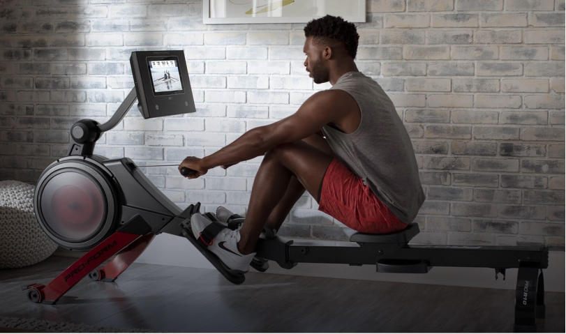 Man using rower with brick wall background